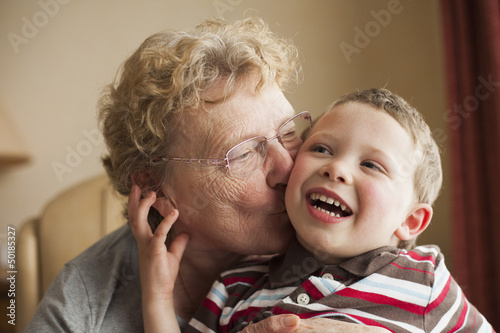 Caucasian grandmother kissing grandson