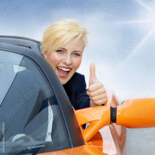 Pretty girl driving a roadster in summer and shows thumb up