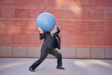 Caucasian businessman carrying heavy ball