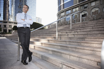 Hispanic businessman standing outdoors with arms crossed