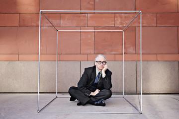 Caucasian businessman sitting inside of box