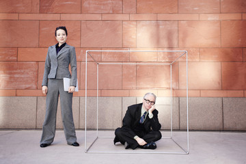 Businesswoman standing next to co-worker in box