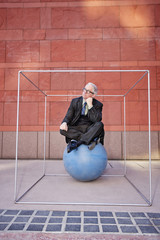 Caucasian businessman sitting on ball inside box