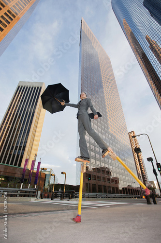 Caucasian businesswoman walking on stilts in urban environment