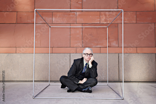 Caucasian businessman sitting inside of box