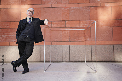 Caucasian businessman leaning on box on sidewalk