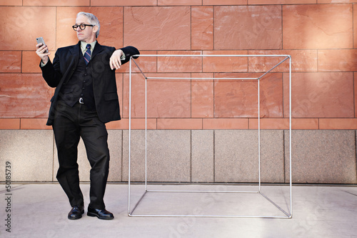Caucasian businessman leaning on box and text messaging on cell phone