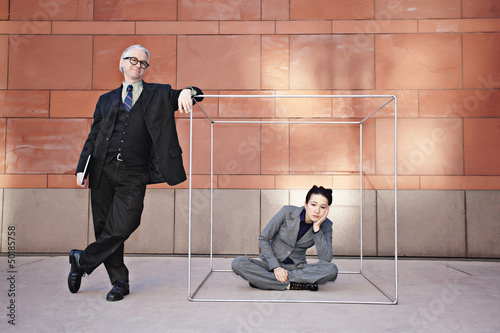 Businessman standing next to co-worker in box