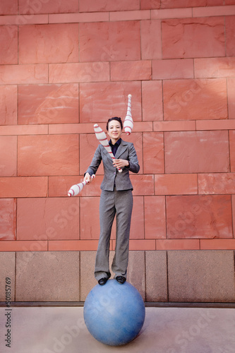 Caucasian businesswoman standing on ball juggling