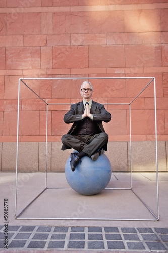 Caucasian businessman practicing yoga on ball inside of box