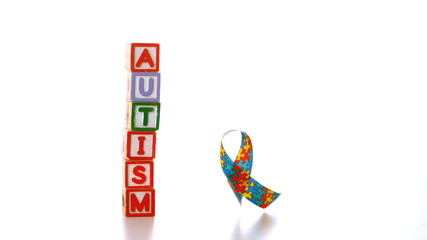 Awareness ribbon dropping beside blocks spelling autism