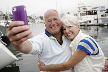 Smiling couple taking self-portrait at marina