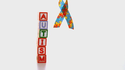 Awareness ribbon falling beside blocks spelling autism