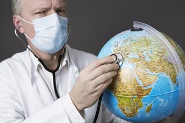 arzt mit stethoskop und globus