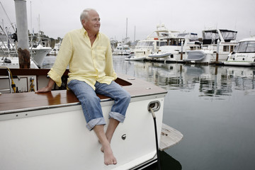 Smiling man sitting on boat in marina