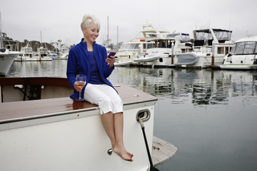 Woman sitting on boat text messaging on cell phone