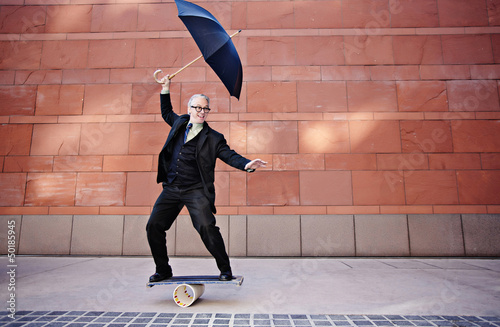 Caucasian businessman holding umbrella and balancing on board