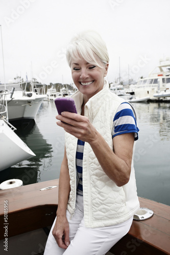 Woman using cell phone in marina