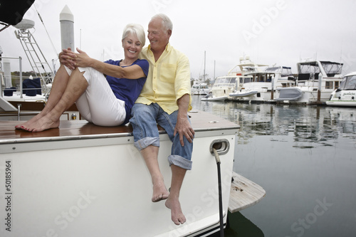 Couple relaxing on boat in marina