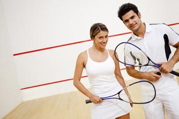 Hispanic couple holding squash racquets