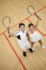 Hispanic couple raising squash racquets