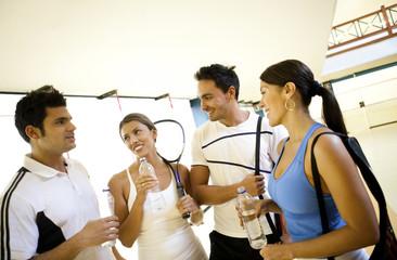 Hispanic couples on squash court drinking water