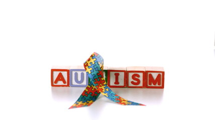 Awareness ribbon onto blocks spelling autism on white background