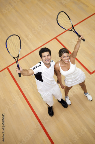 Hispanic couple raising squash racquets