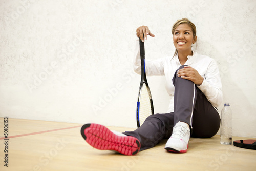 Hispanic woman relaxing on squash court