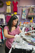 Mixed race woman shopping for children's clothing