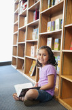 Mixed race girl reading book in library