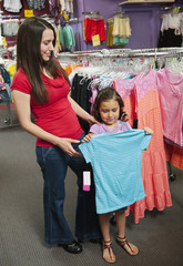 Mixed race mother and daughter shopping for children's clothing