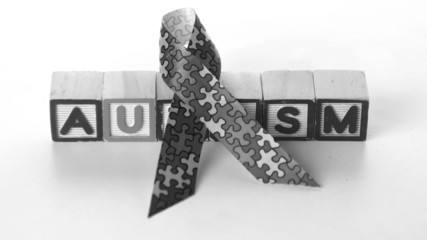 Awareness ribbon front of autism blocks in black and white