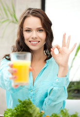 woman holding glass of juice and showing ok sign