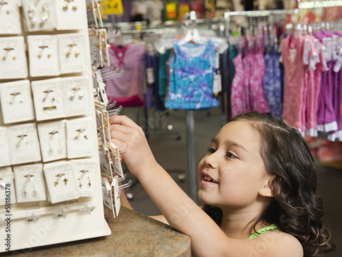 Mixed race girl looking at jewelry in store