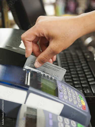 Mixed race woman swiping credit card in store