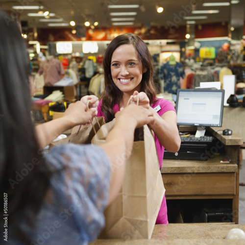 Cashier handing bags to woman in store