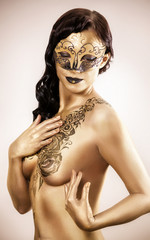 woman in golden paint with drawings on the body