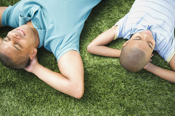 Father and son laying in the grass