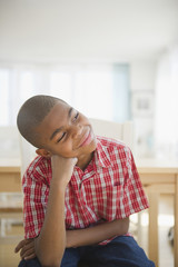 African American boy sitting with head in hands thinking