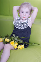 Beautiful little girl sitting on sofa at home with yellow roses
