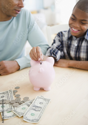Father watching son put coin in piggy bank