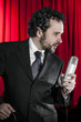 singing man with black suit and microphone on background with re