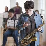 Caucasian student holding cell phone and saxophone in music class
