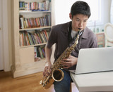 Asian boy playing saxophone looking at laptop