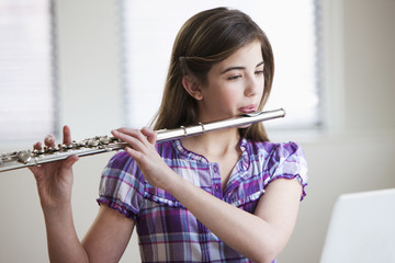 Caucasian girl playing flute