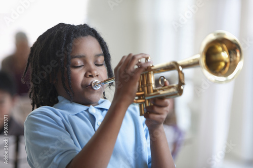 Black student playing trumpet in music class