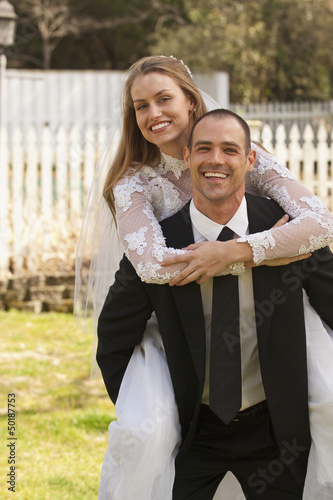 Caucasian groom carrying bride