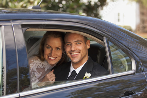 Caucasian bride and groom in back seat of car