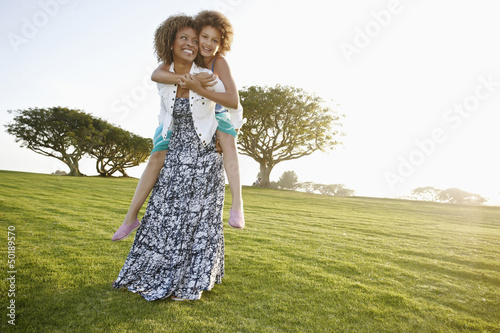 African American mother giving daughter a piggyback ride